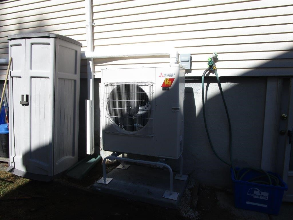 An outdoor condenser and heat pump installed outside a Brighton, MA, home.