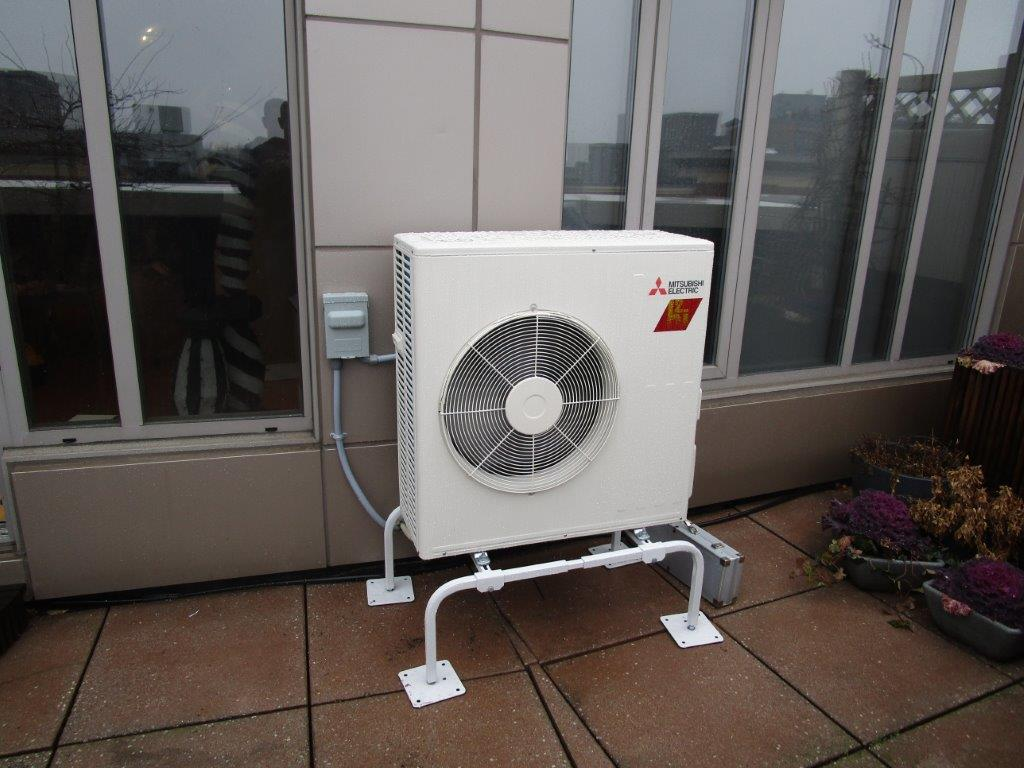 Balcony installation of outdoor unit for ductless system in Boston.