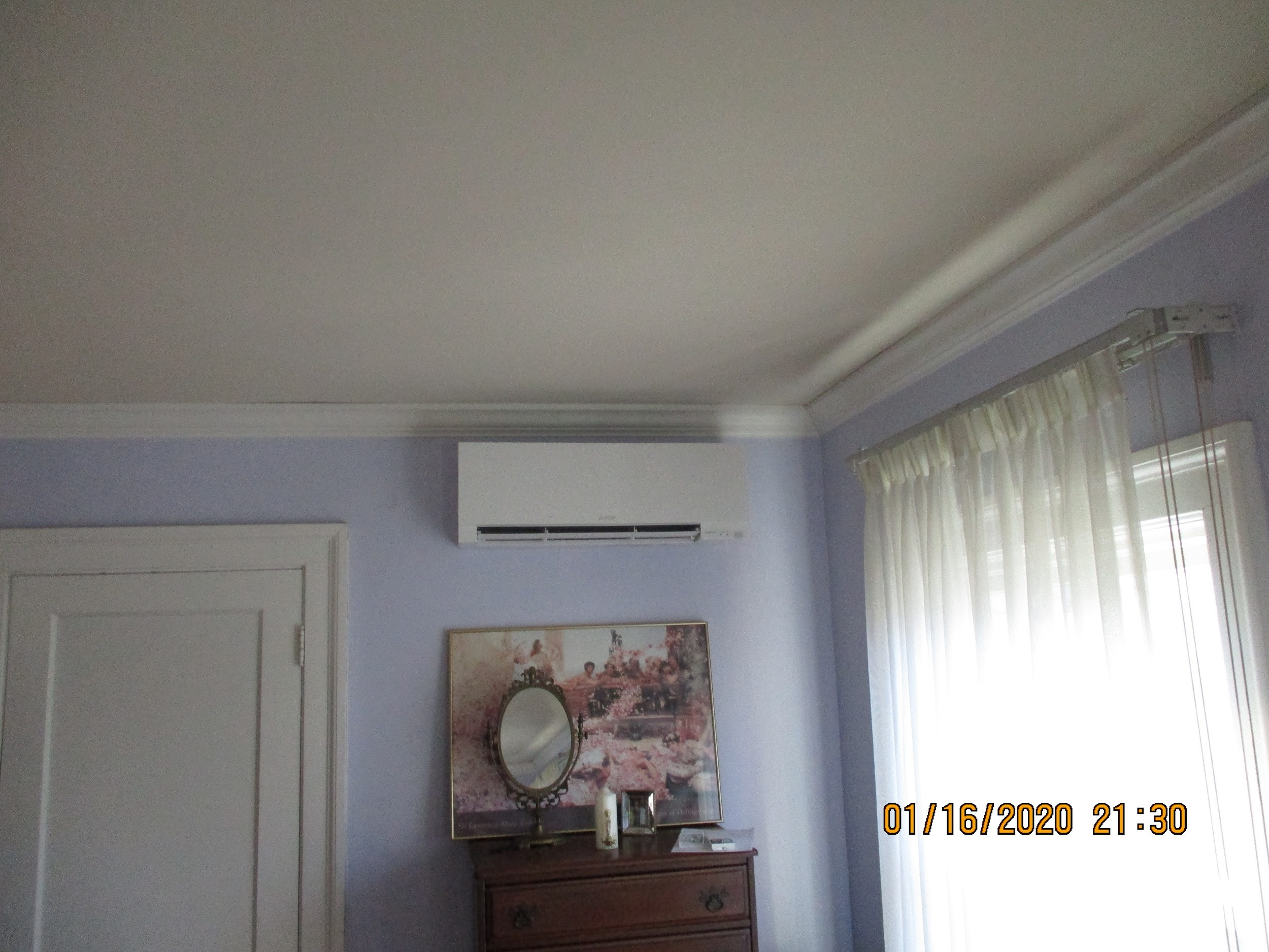 Indoor Mitsubishi ductless AC installed in a bedroom.