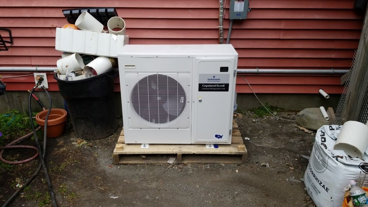 Outdoor condenser unit improperly installed behind a grocery store in MA.