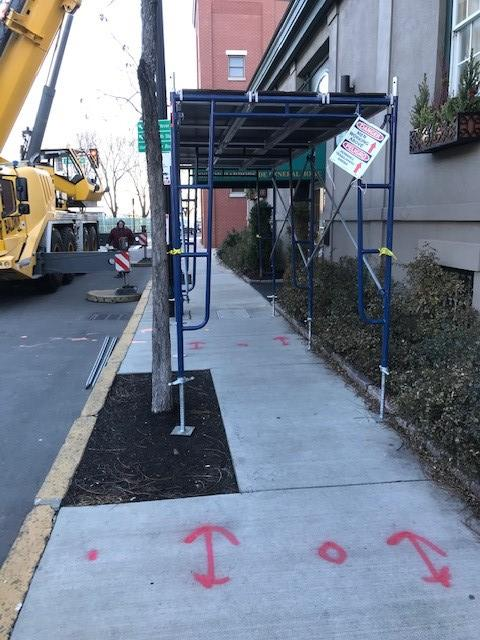 Staging for pedestrians during N.E.T.R. Inc. replacement of old heating unit.