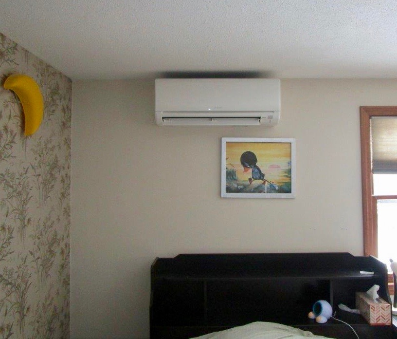 Indoor installation of wall unit for ductless heating and air in the bedroom.