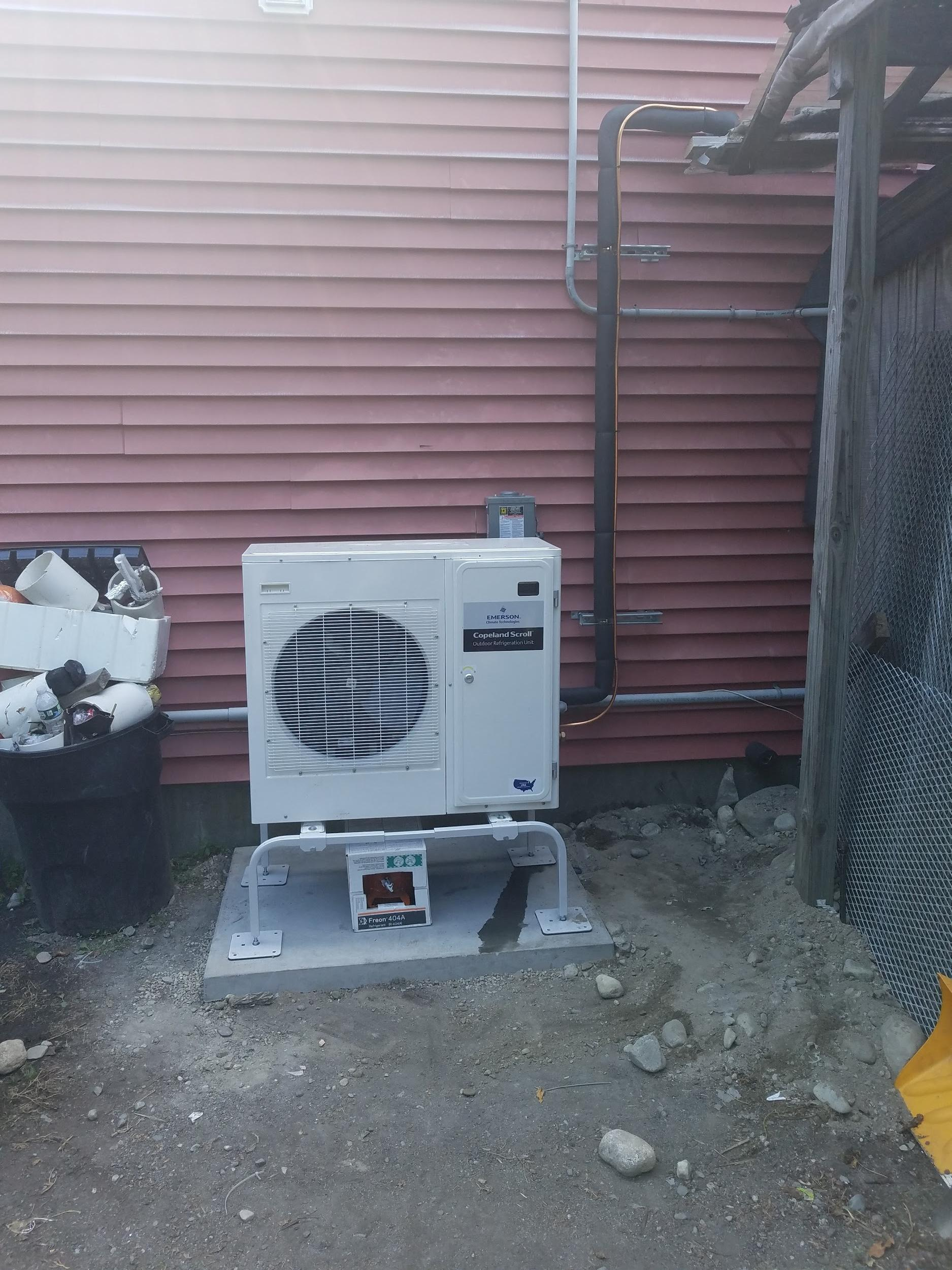 Properly installed condenser unit for a refrigeration system placed on a poured concrete pad.
