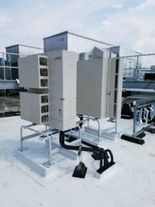 Mitsubishi ductless AC system condenser installed on the roof on the Moderna building.