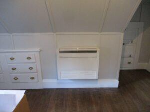 A floor-mounted Mitsubishi ductless AC installed in a bedroom in Swampscott home.