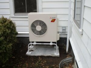 An outdoor air handler heat pump installed outside Boston two-family home.
